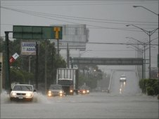 Cars drive along a flooded street in Matamoros, Mexico. Photo: 30 June 2010