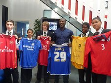 Chris Powell poses with pupils and some of his football shirts