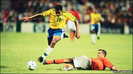 Emerson skips over Philip Cocu during the semi-final between Brazil and the Netherlands in 1998