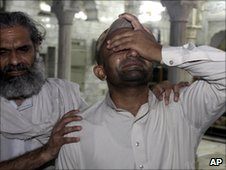 A man is comforted after the bombings in Lahore - 1 July 2010