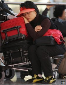 Passenger sleeps on her luggage