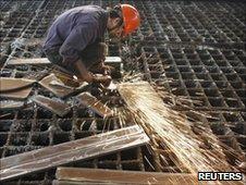 A labourer welds steel frames at a steel factory in Huaibei