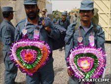 Afghan police recruits wearing flowers in the shape of heart around their necks