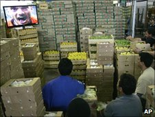 Workers in a market in Sao Paulo watch the Netherlands score