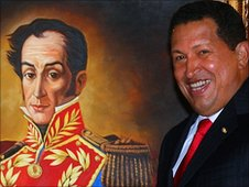 Venezuelan Hugo Chavez stands next to a portrait of Simon Bolivar