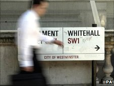 A commuter walks past the Whitehall road sign