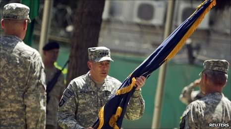 Gen David Petraeus holds a flag during the assumption-of-command ceremony in Kabul on 4/7/2010