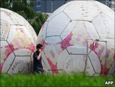 A man walks past giant footballs in Beijing