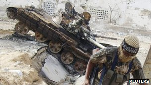 Al-Shabab fighter runs away from burnt-out tank