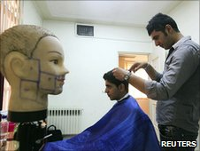 A barber cuts hair at an official hairstyle show in Tehran