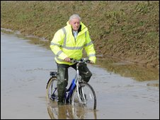 Councillor Roy Pegram trying to cycle through flooding near busway track