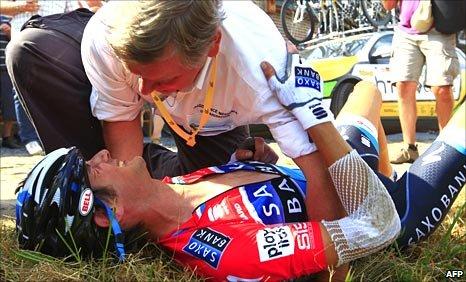 Frank Schleck receives medical assistance from Tour de France doctor Gerard Porte following his crash
