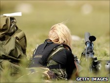 A female police marksman keeps watch over the countryside around Rothbury
