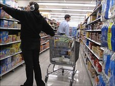 Shopper wearing headphones with a trolley