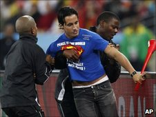 Unidentified man is escorted from the pitch during World Cup match between Spain and Germany