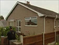 A policeman stands outside the house in Colwyn Bay