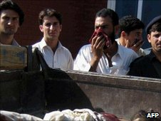 Pakistani residents look at the bodies of militants killed in a military operation in Lower Dir on July 6, 2010