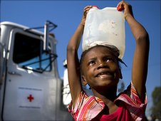 Girl carries water from Red Cross truck in camp near Port-au-Prince