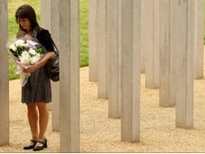 A woman prepares to lay flowers at London Bombings memorial