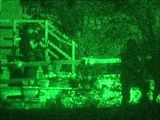 Image taken with night vision camera showing armed police officers