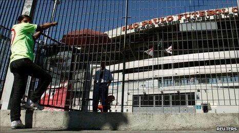 A woman stands in front of the Morumbi soccer stadium in Sao Paulo