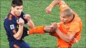 Xabi Alonso is challeneged by Nigel de Jong