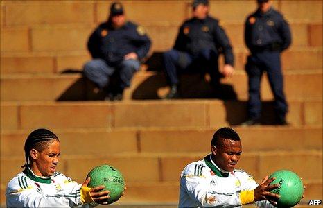 South Africa's midfielder Steven Pienaar (left) and midfielder Kagisho Dikgacoi (right) train in Johannesburg as police watch