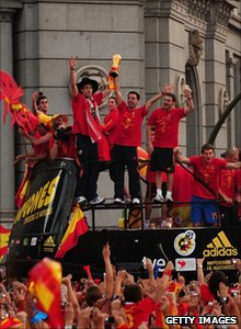 Spanish football players with the World Cup trophy on an open-top bus in Madrid