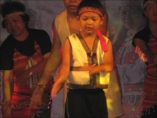 A young boy performs an indigenous dance