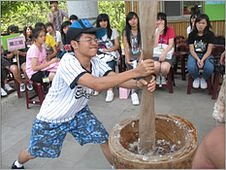 Boy pounding millet flour to make mochi