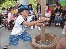 Boy pounding millet flour to make mochi