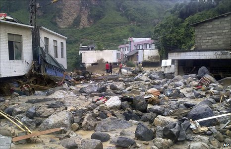 People stand amid rubble caused by a landslide in Xiaohe on 13  July 2010