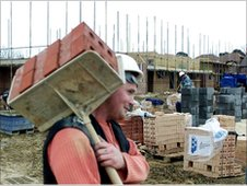 A builder carrying bricks