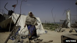 A woman stands next to the remains of her home in Gaza, which was destroyed during the Israeli offensive on Gaza in 2008/9 (4 June 2010)