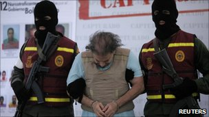 "Colombian Carlos Alberto ""Beto"" Renteria is escorted handcuffed by Venezuelan secret police"