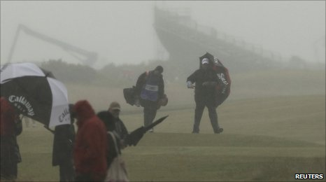 Players and spectators battle to withstand the elements