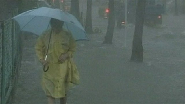 Woman with umbrella walking down flooded street