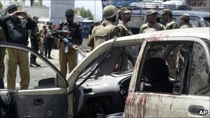 Pakistani soldiers and police officers at the site of the bombing in Mingora
