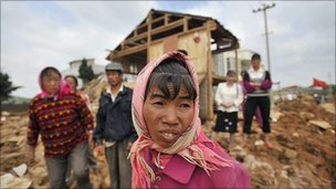 Villagers stand in front of their houses destroyed by floods in Yunnan province