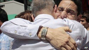 Cuban dissidents Normando Hernandez, right and Omar Rodriguez hug on arrival at a hostel in Madrid, on 14 July 2010