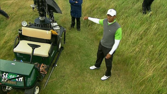 Tiger Woods points at the buggy touching his ball