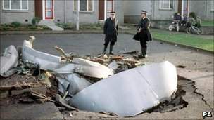 Police officers standing among debris in Lockerbie