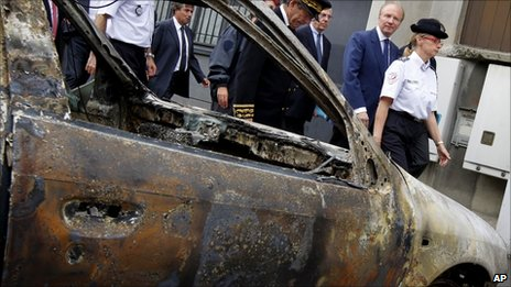 Interior Minister Brice Hortefeux (second from right) passes a charred car in Grenoble, 17 July