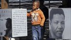 Boy stands next to images and words about Nelson Mandela