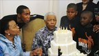 Nelson Mandela blowing out candles on his 92nd birthday cake