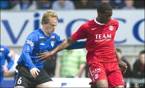 Peterhead defender Neil McVitie is held off by Conor Okus