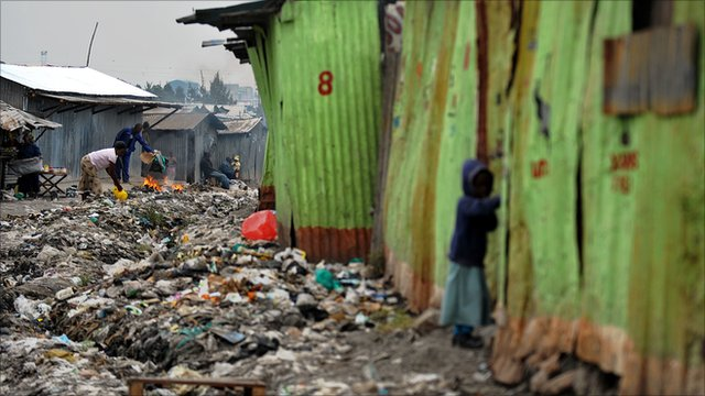 Slum residents stand among strewn rubbish in Nairobi&#039;s Mukuru-kwa-Njenga slum