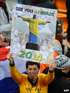 "Supporter holds sign reading ""See you in Brazil in 2014"""