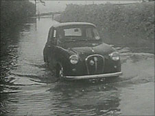 Car in flood water, 1960