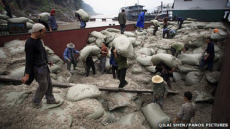 Labourers unload sacks of asbestos from a barge in Chongqing, China